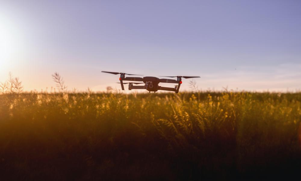 A quadcopter drone flying over agriculture land